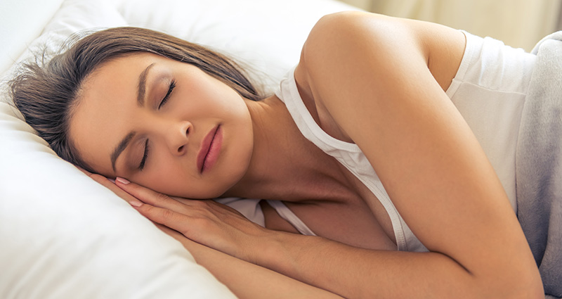 Adult woman sleeping in her bed at home after using cbd gummies for sleep. Buy cbd gummies for insomnia.