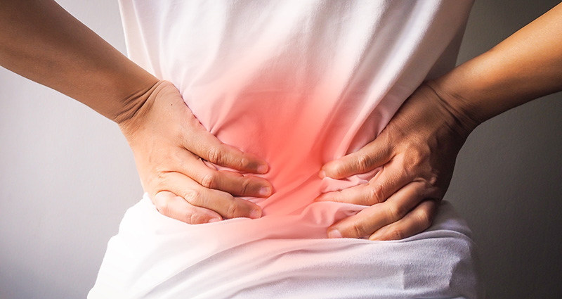 woman with lower back pain lumbar pain in need of CBD oil for pain management.